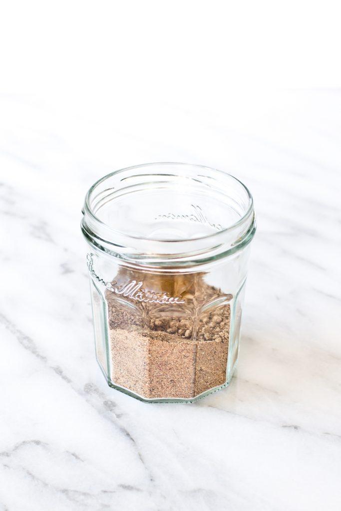 Side view of Mekelesha spice blend in a mason jar